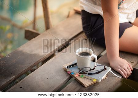 Notebooks pen glasses and coffee cup are putting down on the wood waterside while young woman sitting beside them in morning time on weekend