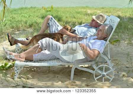 Senior couple relaxing near  hotel resort with dog