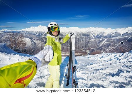Woman walk and pull man with holding hand wearing ski outfit in the mountains looking back and smile