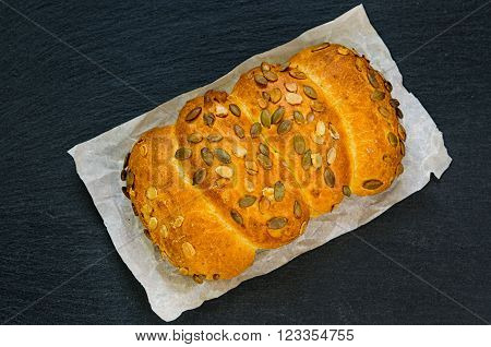 Rustic home made bread loaf with pumpkin seeds on black slate stone board