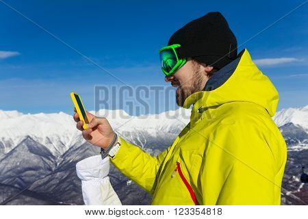 Man skier with beard and ski mask text holding phone standing on top of the mountain