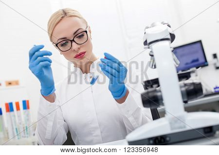 Portrait of beautiful young scientist making analysis of blue liquid. She is holding a pipette and flask. The woman is sitting at the desk and looking at the tube with seriousness