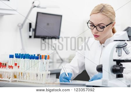 Professional young scientist is recording her research on the paper. She is sitting at the desk and writing with concentration in lab