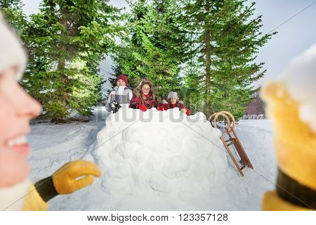 Picture of smiling girl throwing snowball at her friends hiding behind big snow tower, winter outside games