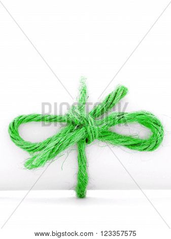Handmade green cord knot tied on white message scroll, isolated