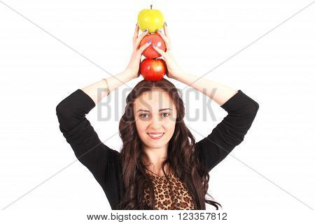 Teen girl holds an three apples on her head isolated on white