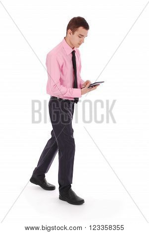 The boy in a pink shirt goes holding tablet PC white background with soft shadow