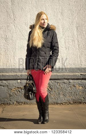 Portrait of smiling young caucasian woman with long blond hair wearing parka and boots carrying a bag standing against a gray wall