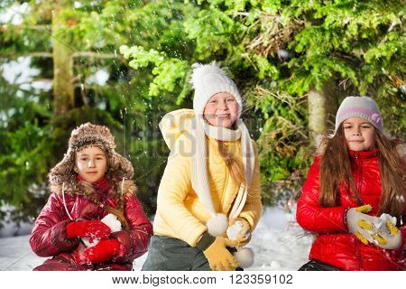 Three girls playing snowballs in the winter forest at sunny day ** Note: Visible grain at 100%, best at smaller sizes