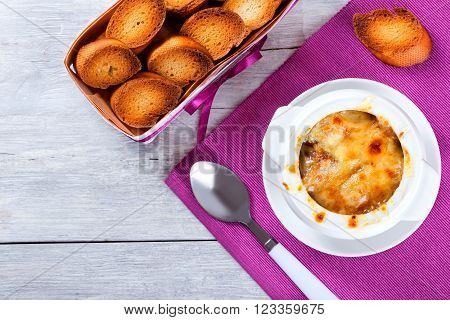 french onion gratin soup in a white pot close-up