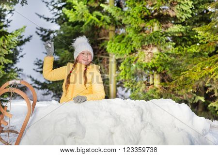 Happy girl throwing snowball from the snow tower in the forest