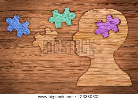 Puzzle head brain concept. Human head profile made from brown paper with a jigsaw piece cut out.