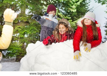 One boy and two girls throwing snowballs hiding after snow tower in the winter forest