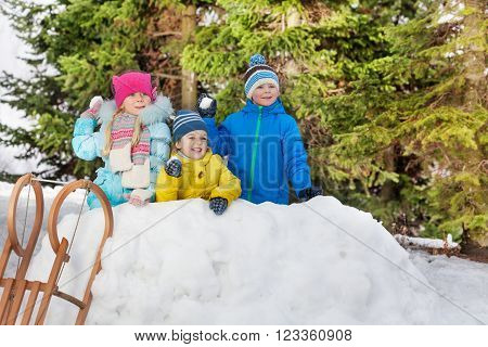 Group of little children in snow fortress throw snowballs
