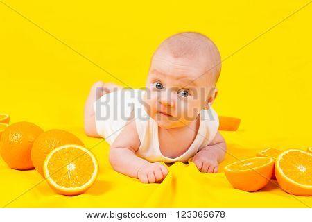 babe lying on the tummy with oranges