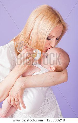 mom feeds the baby bottle in studio