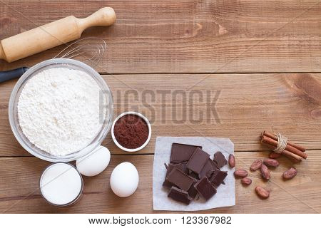 Ingredients for making chocolate chip cookies on a wooden background . Flour sugar egg chocolate cocoa cinnamon vanilla and butter. Close up. Top view