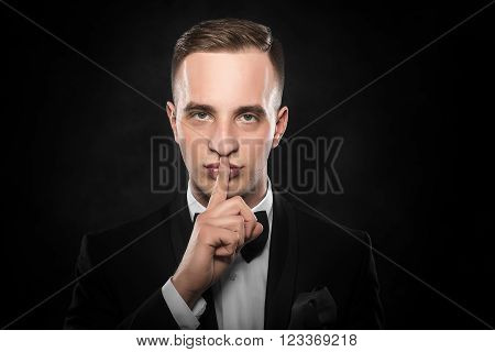 Man gesturing silent on a dark background.