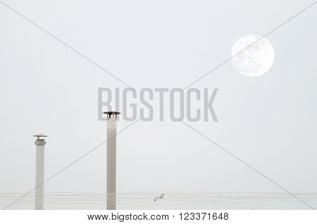 Two smokestacks and the moon while a seagull is flying crossing a grey sky. Empty copy space for editor's text.