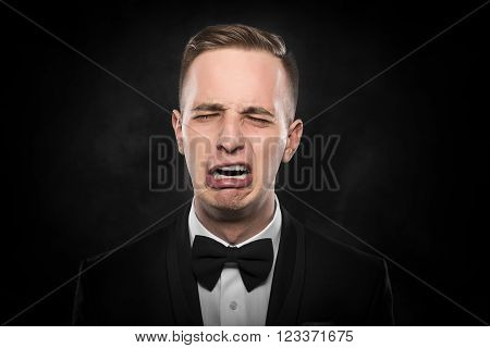 Depressed crying man in black suit over grey background.