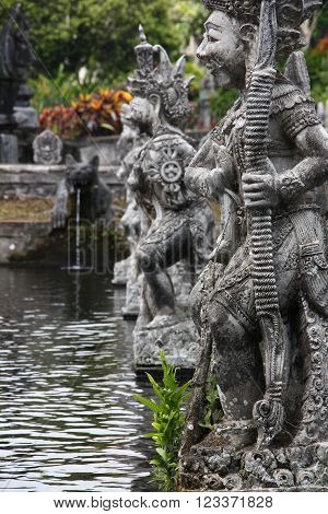 Traditional Balinese Warrior's Sculptures in sacred garden of Tirtaganga Bali. Some sculptures are in open water and some trees and flowers around.