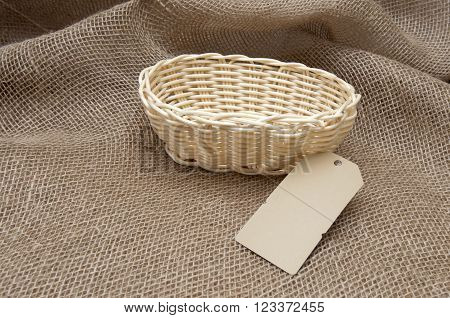 New wicker basket on the background of burlap.
