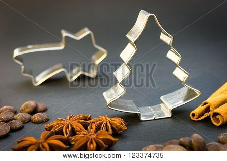Christmas star and Christmas tree cookie cutters, anise stars, cinnamon sticks and chocolate on the black background