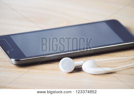 Close up of black smartphone and headphones on wooden table