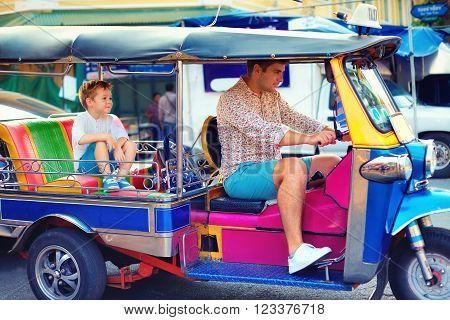 Happy Tourist Family Having Fun On Traditional Tuk-tuk Taxi In Asian City