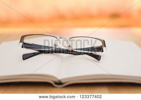 Glasses and diary on wood table in warm tone