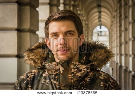 Young man from Warsaw (Poland) in a winter jacket next to an old building with stone arches