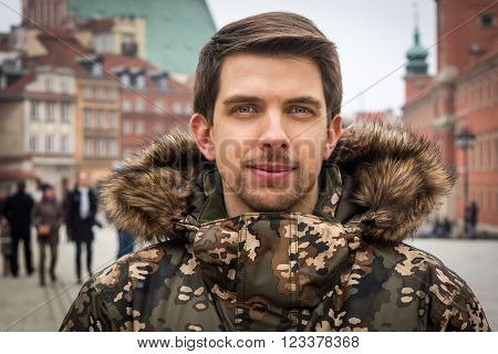 The young man from Warsaw (Poland) in a winter jacket in the old town, the royal castle in the background