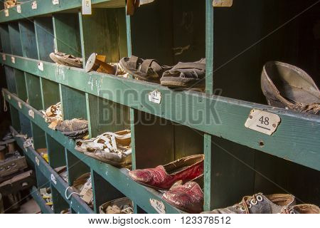 Worn and aging shoes in wooden cubby.