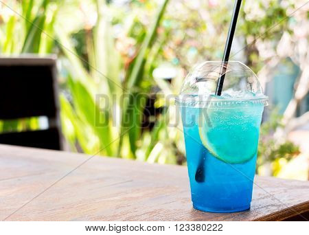 ice blue lemon soda on wooden table in restaurant represent refreshment in summer