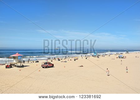 HUNTINGTON BEACH, CA - MARCH 25, 2015: Huntington Beach Shoreline with lifeguard stations and beach goers on a sunny Spring day.