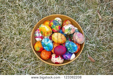 Colorful easter eggs im a bowl on a drosted old grass