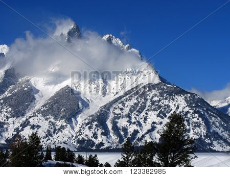 Snow mist blowing over Grand Tetons Mountain Range