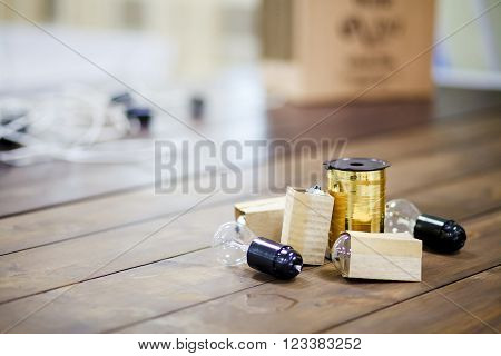 Incandescent bulbs with a coil of golden ribbon on the wooden table. Making garland of bulb lamp, decoration of events. Copy space for your text.
