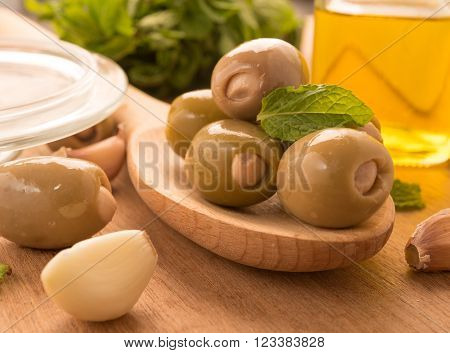 Green olives on a wooden spoon garnished with basil garlic near glass bowl and olive oil jar