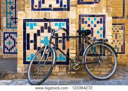 Old bicycle against the wall at ancient building on old street of Bukhara Uzbekistan