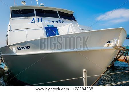 Waikiki, Honolulu, Hawaii, USA - December 13, 2015: Atlantis Discovery boat moored at it's private tour jetty. This boat belongs to the Atlantis Submarines Waikiki underwater charter tour company.