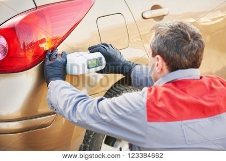colourist man selecting color of car with paint matching scanner