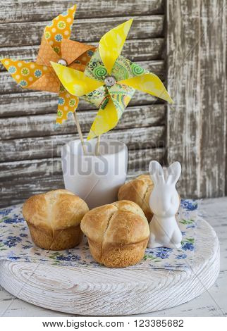 Sweet brioche, Easter ceramic rabbit and homemade paper pinwheel, on a light wooden rustic background