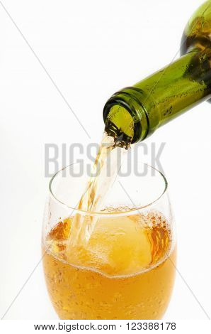 Pouring white wine from bottle into the wineglass on white background
