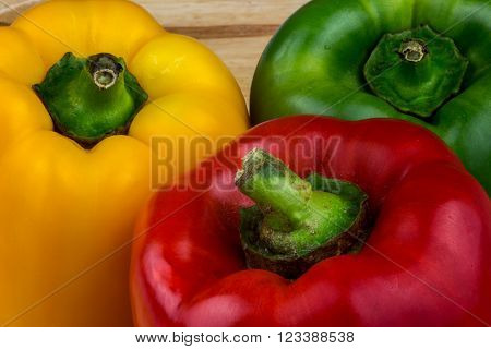 Fresh red green and yellow capsicums on a wooden surface