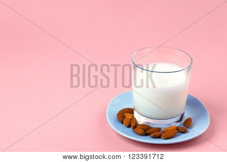 Galss of almod milk on a pale blue plate on a pink surface
