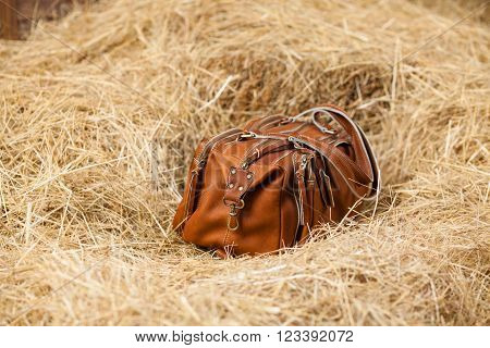 leather bag on a background of yellow hay