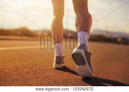 Running sport shoes on runner. Legs and running shoe closeup of man jogging outdoors on road.