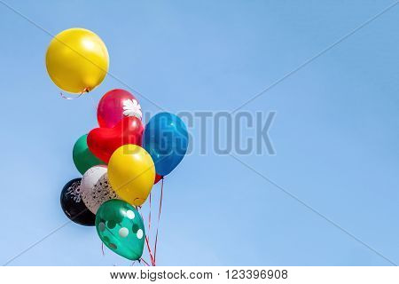 Colorful Balloon Floating In Mid Air Against A Bright Blue Sky.