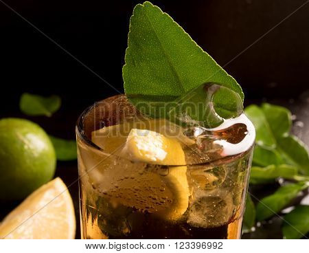 glass of cola  with ice cubes, lemon slice and mint